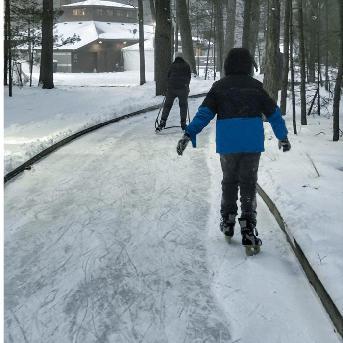 kids on ice skating trail through the woods at Muskegon Luge Adventure Sports Park