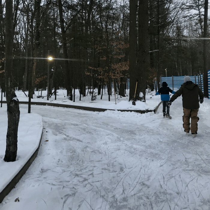family on ice skating trail through the woods at Muskegon Luge Adventure Sports Park