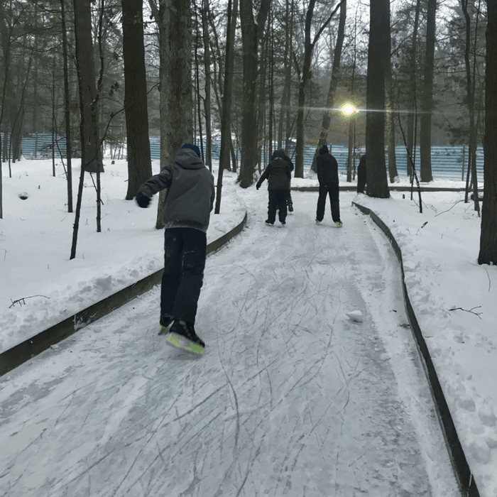 teenager on ice skating trail through the woods at Muskegon Luge Adventure Sports Park at night