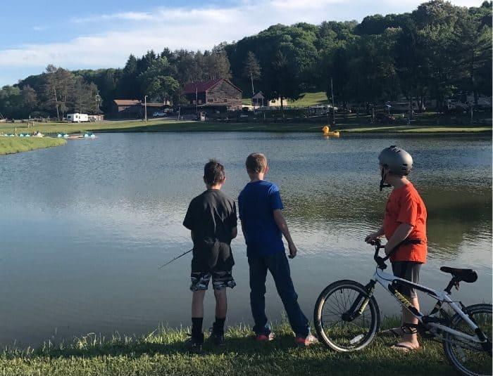 kids fishing next to a boy on a bike