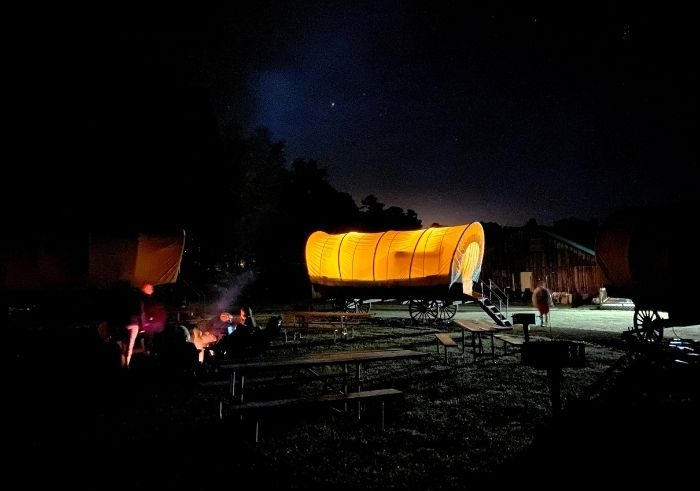 Covered wagons at Sheltowee Trace Adventure Resort at night