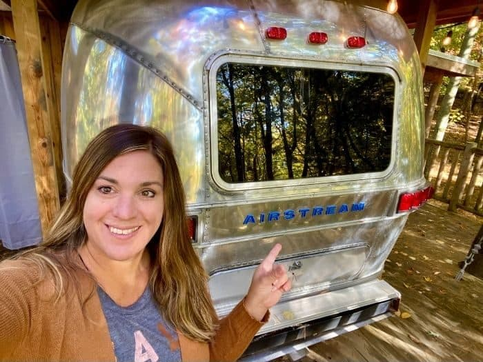 Nedra McDaniel outside The Silver Bullet Airstream Treehouse