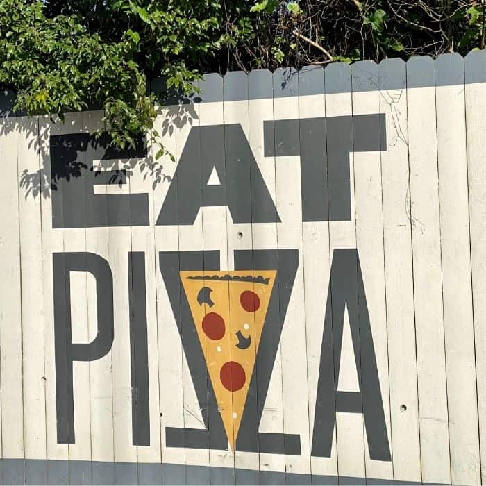 Eat pizza sign at Crown Pizza