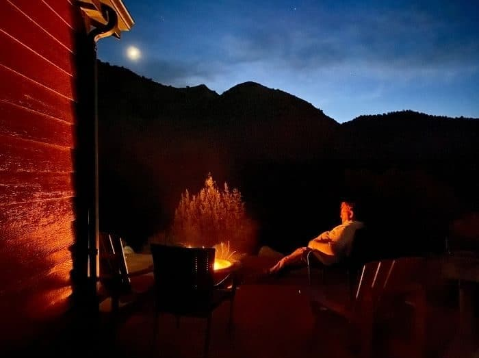 man at fire pit for deluxe cabin at Cannonville Bryce Canyon KOA