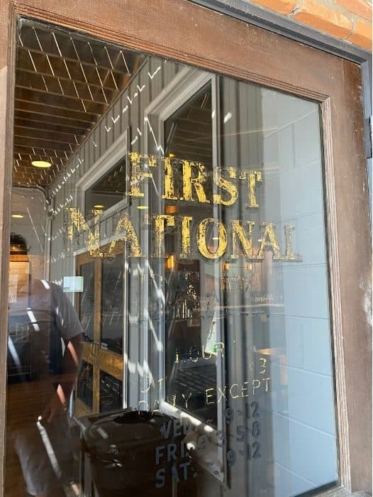 faded First National Bank sign on a door