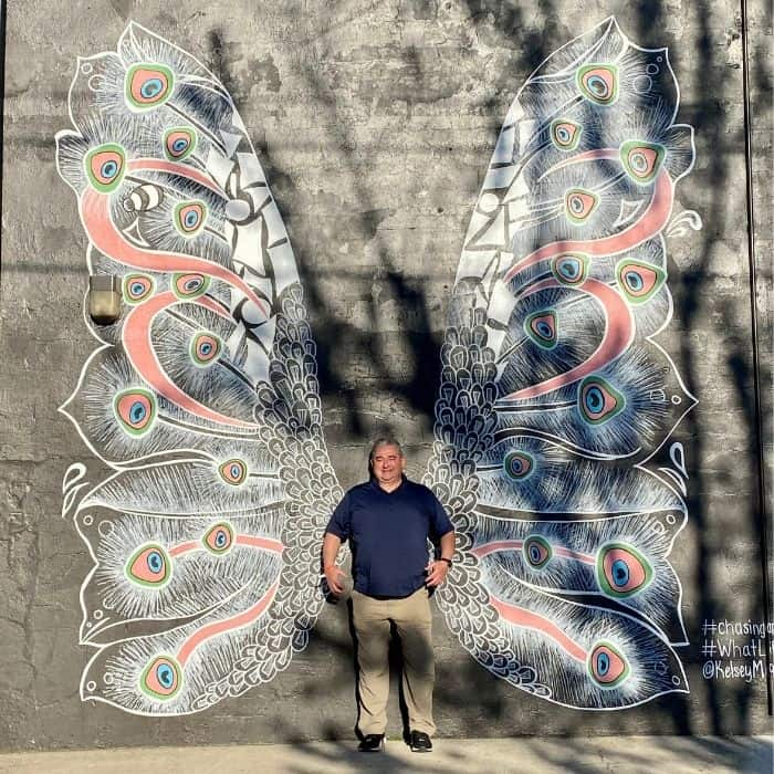 man in front of angel wing mural on the The MoCo Mural Trail