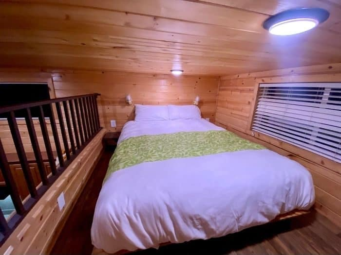 queen size bed in bedroom of deluxe cabin at Flagstaff KOA Holiday