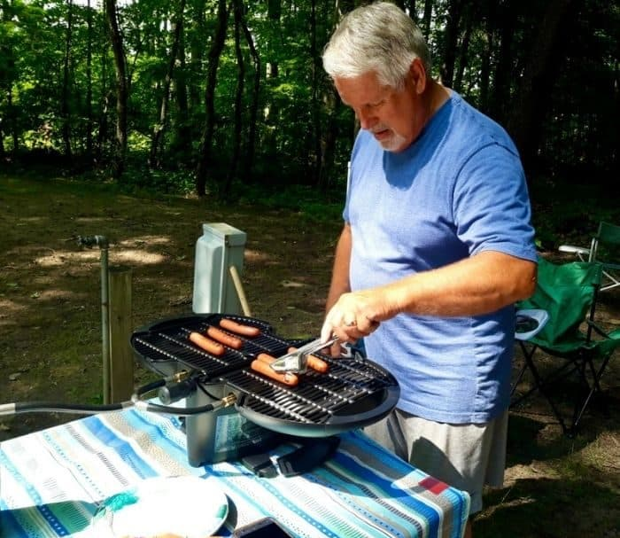 man cooking hot dogs on the nomadiQ grill