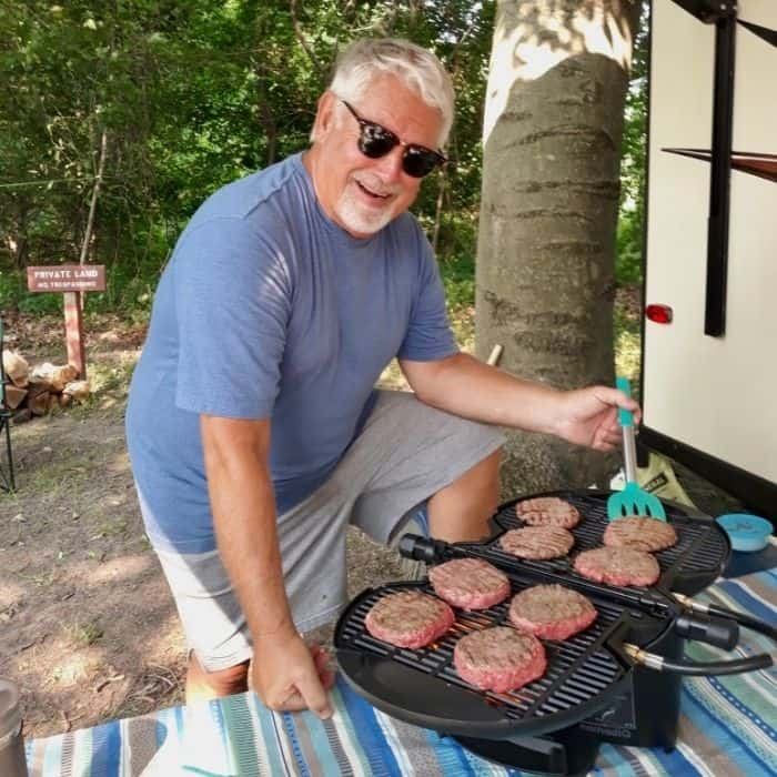 man grilling burgers on portable grill