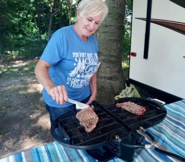 woman grilling steaks on a portable grill