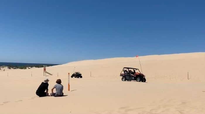 boys- watching- off-road-vehicles-on -sand-dunes