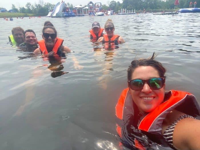 friends in lake wearing life jackets